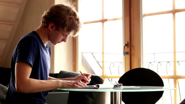 A left-handed male young student working on a creative homework video