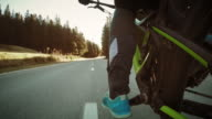 POV Leg of biker pedaling on countryside road in sunshine video