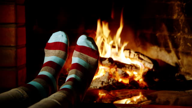 Legs in socks on the background of a burning fireplace video
