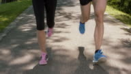 SLO MO TS Legs of a couple running in park video