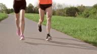 SLO MO TS Legs of a couple running on asphalt video