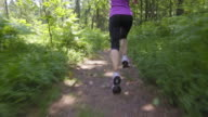 SLO MO TS Legs of female running along forest path video