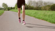 SLO MO TS Legs of running woman moving on asphalt video