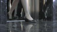 LD Legs of business people as they exit the elevator video