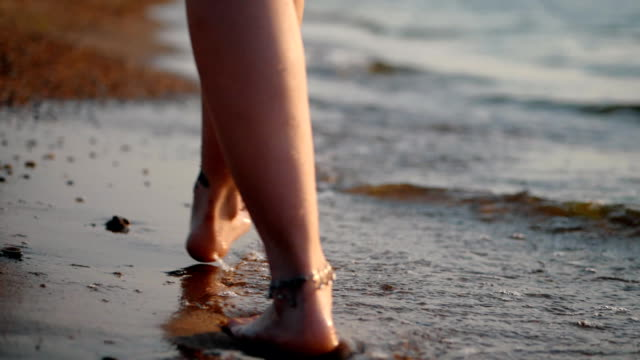 Legs of caucasian girl wearing shorts and walking barefoot wet sand sea beach, sun, lens, flare. Slow motion. Woman walks away from the camera video