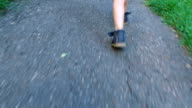 Legs of child striding across asphalt path. Green grass growing along the track. video