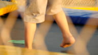 legs of children running and jumping on the trampoline video