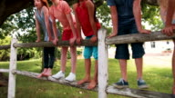 Legs of children standing on a wooden fence in park video
