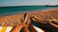 Legs of Couple People Lying on Beach Sun Lounger near the Red Sea video