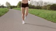 SLO MO TS Legs of female marathon runner on asphalt video