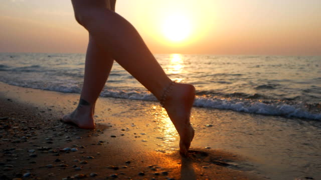 Legs of Hispanic girl walking barefoot wet sand island beach sun lens flare. Beautiful feet of young woman near sea on sunset or sunrise. Slow motion video