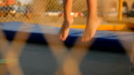 legs of kids running and jumping on the trampoline video