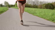 SLO MO TS Legs of male runner moving on asphalt video