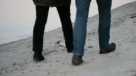 Legs of man and woman walking on the beach step for step video