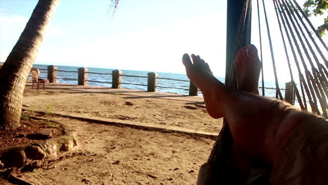 Legs of person relaxing in a hammock by sea, afternoon video