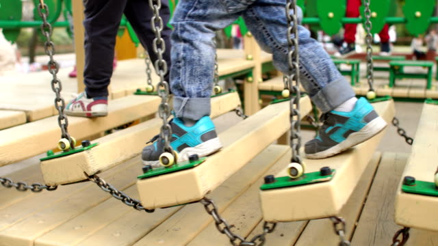 Legs of the child on a wooden bridge. Playground. video