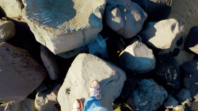 legs of walking man in a frame, selfie moving shot, walking on huge stones in sunny weather video