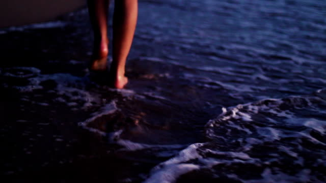 Legs only young blonde girl walking barefoot along wet sand beach. Sunset Evening Romantic Instagram Color Tone. video
