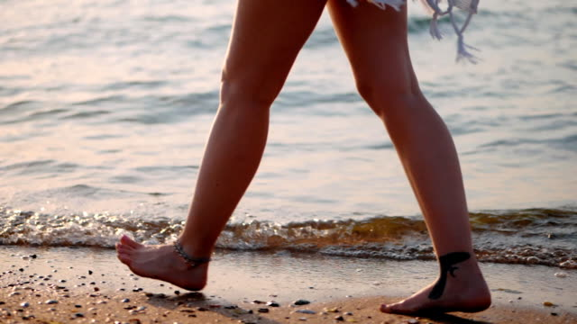 Legs with tattoo of caucasian girl wearing shorts and walking barefoot wet sand sea beach, sun, lens, flare. Slow motion. Side view video