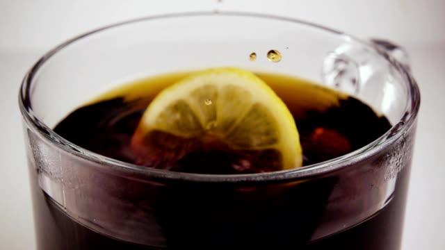 Lemon drops into a glass with tea. Slow motion video