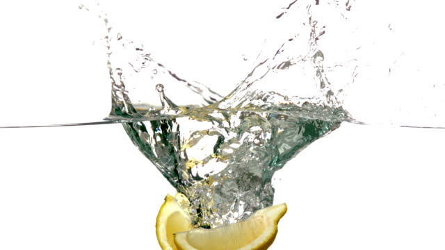Lemon segments plunging into water on white background video