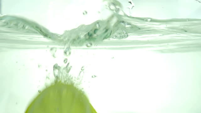 Lemon slices drop in the water. Close up. Slow motion. video