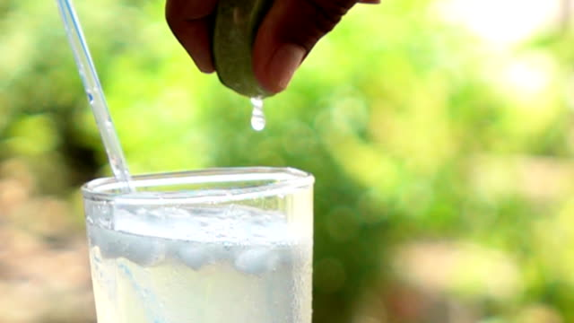 Lemon squeezing into glass of water,Slow motion video