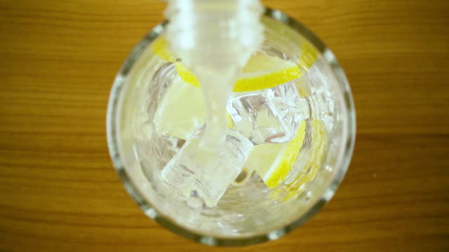 Lemon water pours into a glass with ice top view. Slow mo video