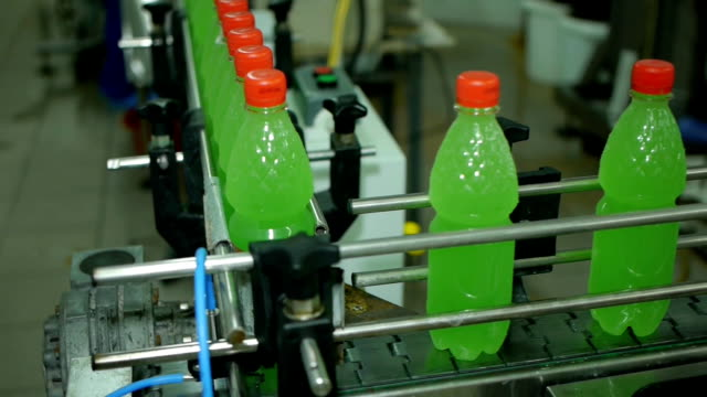 lemonade soda bottles move along the conveyor belt are filled with packed twist on the production video