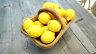 Lemons in a basket on a wooden table video