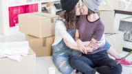 Lesbian couple kissing while unpacking for the new home video