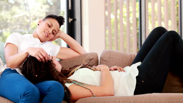 Lesbian couple lying together on the couch video