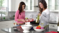 Lesbian couple preparing meal together and drinking wine, shot on R3D video
