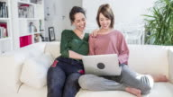 Lesbian couple searching holidays on a laptop video