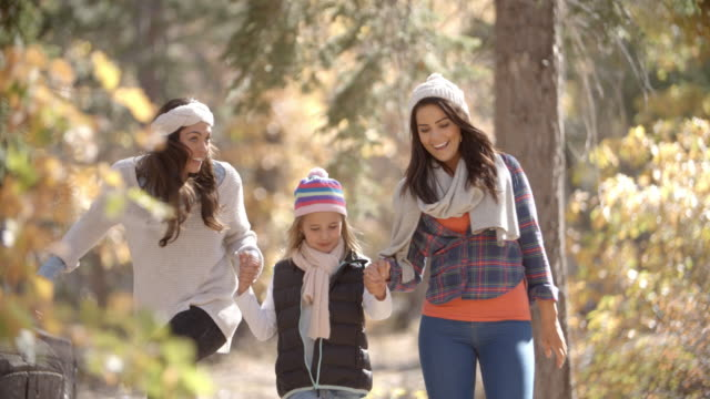 Lesbian couple walking in a forest with their daughter video