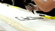 Letter F. Baker confectioner wrote the letter F on the big cake using a pastry bag video