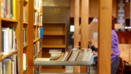 Librarian pushing trolley through the library returning books video