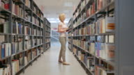 DS Library users searching for books in the aisles video