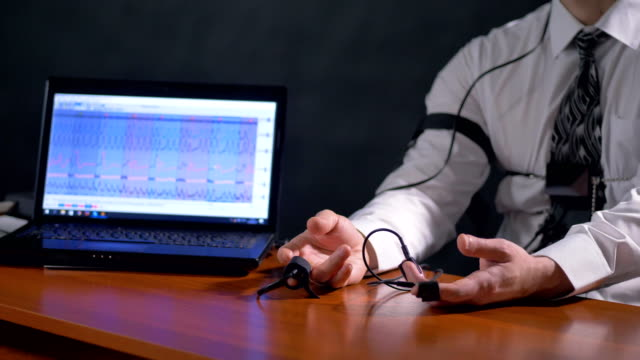 A lie detector test subject rests hands on a table. video