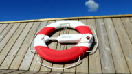 Life belt hanging on wooden pier or boat at midday video
