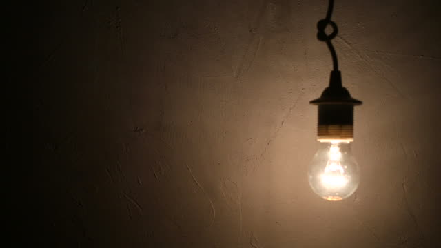 light bulb flickering against concrete wall video
