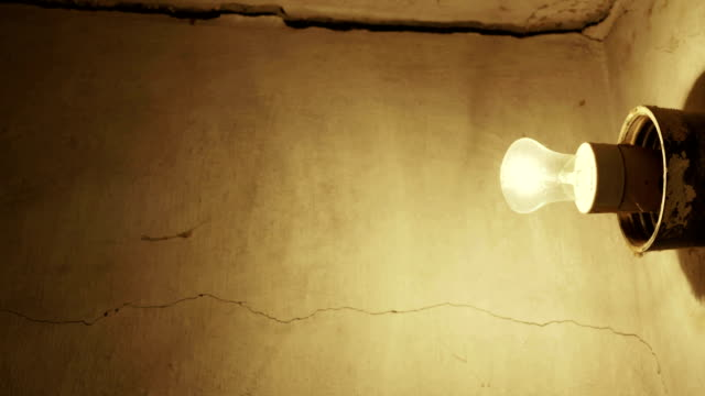 Light bulb glowing on grunge concrete wall in old house video