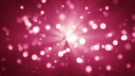 Light rays with glitter particles bokeh red background video