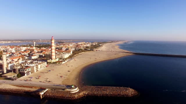 Lighthouse on the beach Praia Velha, Barra, Aveiro, Portugal aerial view video