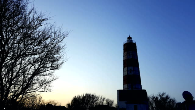 lighthouse with rotating spotlight during sunset video