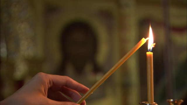 Lighting a votive candle in church with icon video