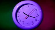 lilac Clock on color wooden plank wall, night video
