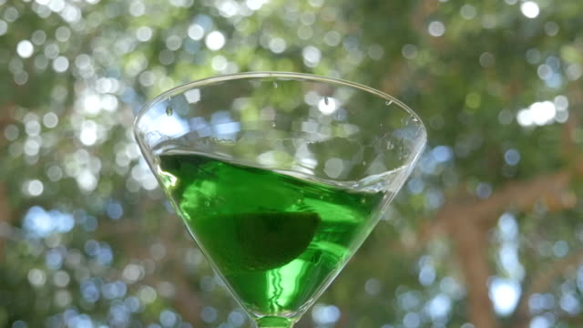 A Lime Drops into a Bright Green Appletini in Slow Motion video