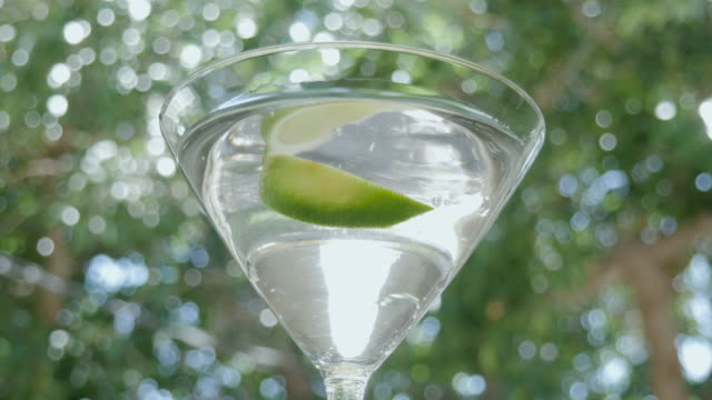 Lime Drops into a Martini Cocktail in 4k video