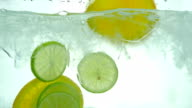 Lime, Lemon and orange slices drop in the ice water. Close up. Slow motion. video